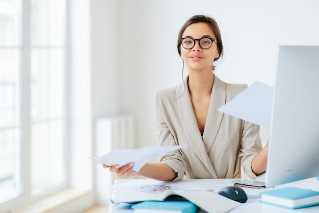 Frau im büro, umgeben von dokumenten