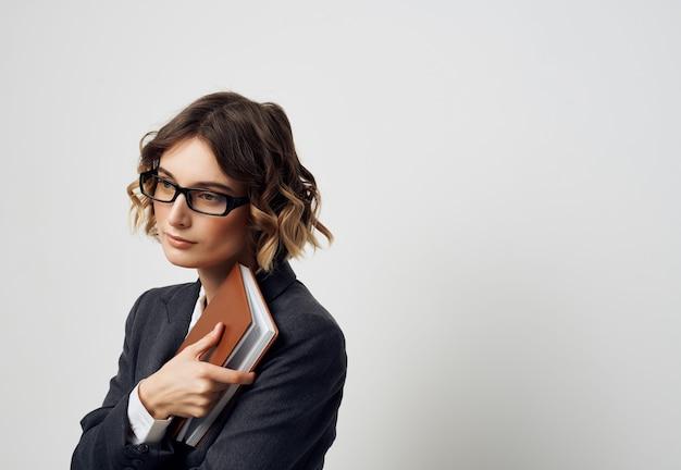 Frau im business-anzug-notizbuch in der hand heller hintergrund