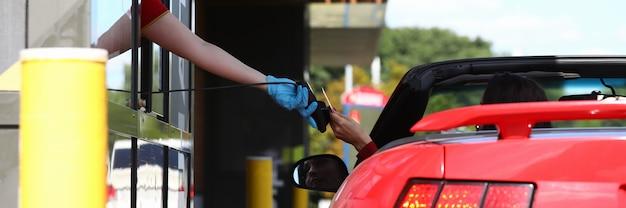 Frau im cabrio zahlt mit bankkarte am zahlungspunkt