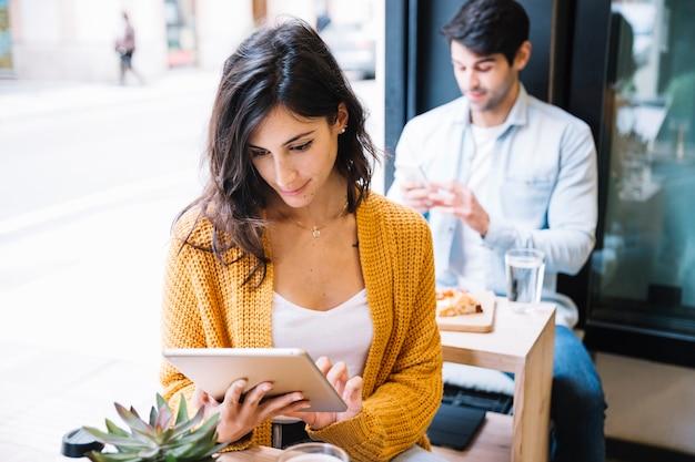 Frau im café, das an tablette arbeitet