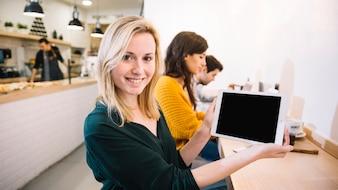 Frau im Café, das Tablettenschirm zeigt