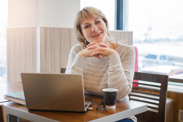 Frau im café und im büro, die mit laptop arbeitet