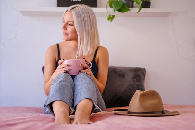 Frau im dekorierten schlafzimmer, das kaffee trinkt