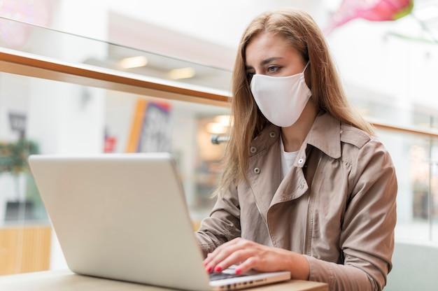 Frau im einkaufszentrum, das am laptop arbeitet und maske trägt