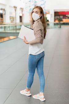 Frau im einkaufszentrum mit laptop, die maske trägt