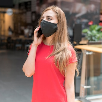 Frau im einkaufszentrum mit maske, die auf handy spricht