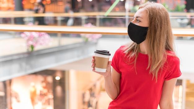Frau im einkaufszentrum mit maske und tasse kaffee