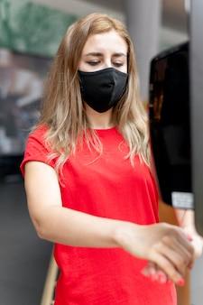Frau im einkaufszentrum mit maske unter verwendung des händedesinfektionsmittels