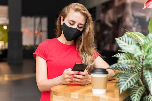 Frau im einkaufszentrum mit maskenprüfmobil