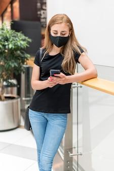 Frau im einkaufszentrum trägt maske und prüft handy