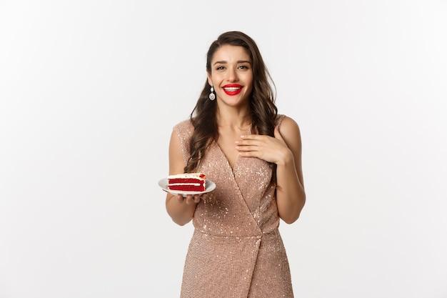 Frau im eleganten kleid, das ein stück kuchen hält