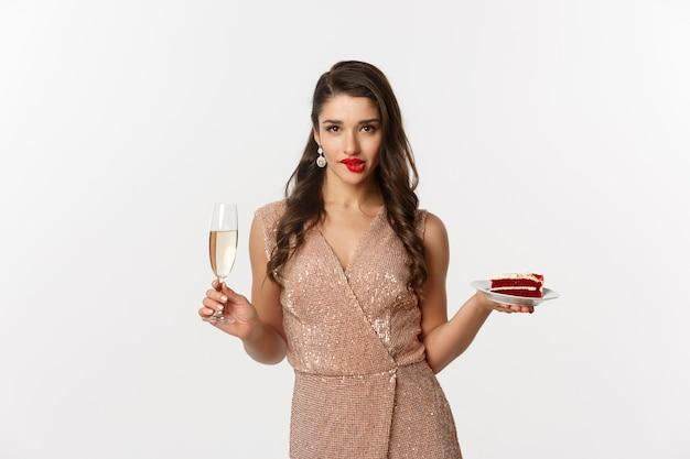 Frau im eleganten kleid, das ein stück kuchen und ein glas champagner hält