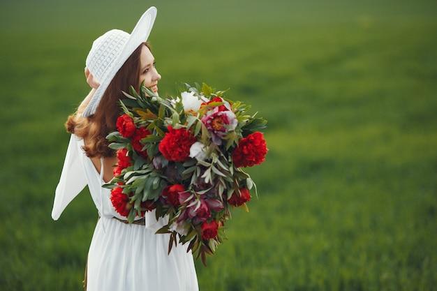 Frau im eleganten kleid, das in einem sommerfeld steht
