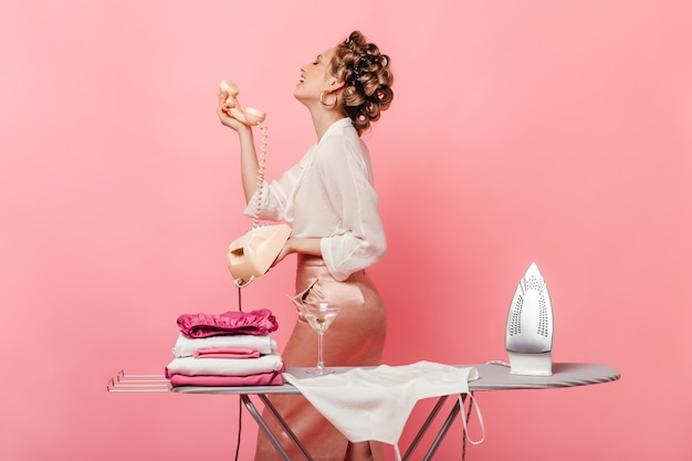 Frau im eleganten outfit lächelt und spricht am festnetztelefon und posiert auf rosa wand mit eisen