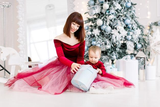 Frau im eleganten roten kleid, sitzt mit ihrem kleinen baby und spielt mit geschenk