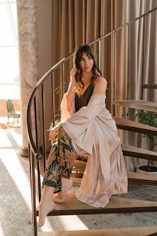 Frau im eleganten sexy haus tragen genießenden morgen im stilvollen wohnzimmer.