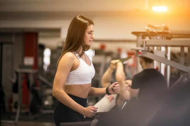 Frau im fitnessstudio auf einer laufenden maschine