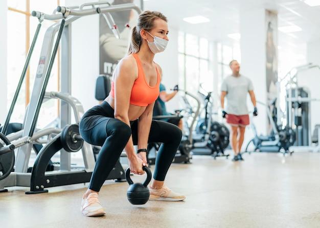 Frau im fitnessstudio beim training mit maske