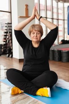 Frau im fitnessstudio macht yoga