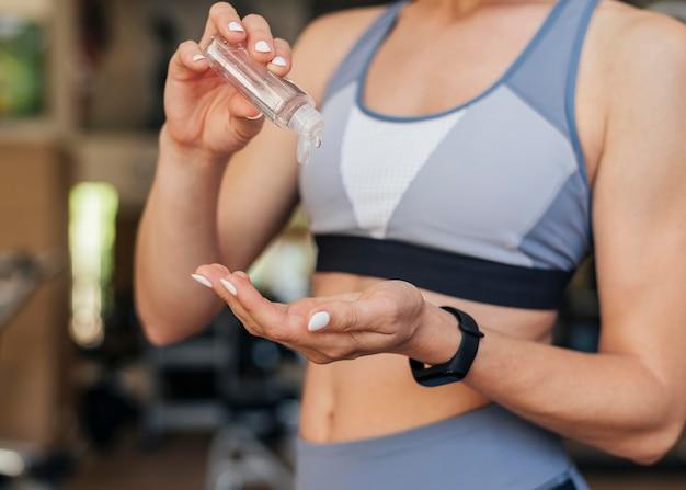 Frau im fitnessstudio mit händedesinfektionsmittel