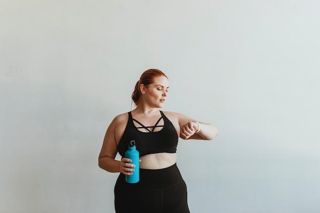 Frau im fitnessstudio schaut auf ihre uhr