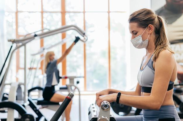 Frau im fitnessstudio unter verwendung der ausrüstung mit der medizinischen maske