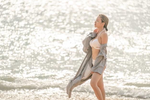 Frau im fliegenden bademantel geht am strand entlang mit meereshintergrund.