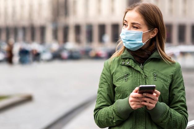 Frau im freien, die eine maske trägt und das smartphone benutzt