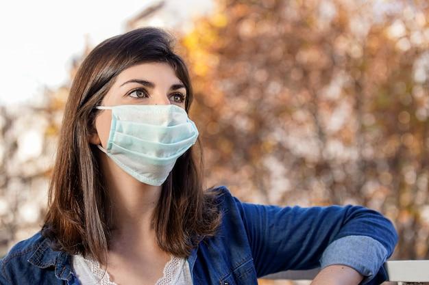 Frau im freien, die eine medizinische schutzmaske trägt. covid 19