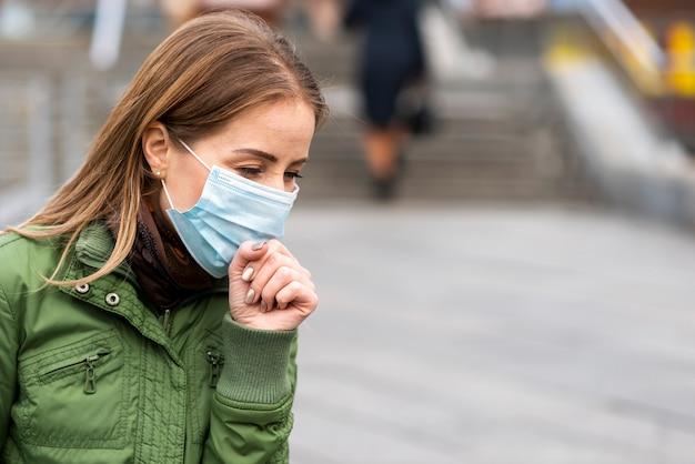Frau im freien, die eine schutzmaske und husten trägt