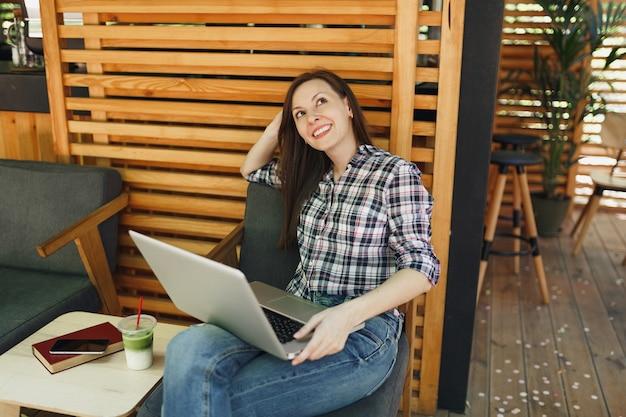 Frau im freien straße sommer café aus holz café sitzen in freizeitkleidung, arbeiten an modernen laptop-pc-computer