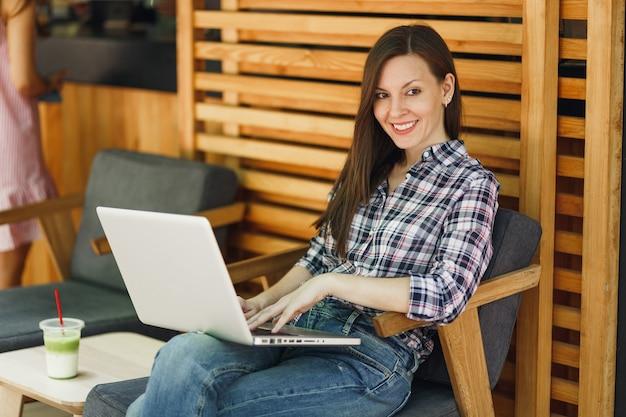 Frau im freien straßensommerkaffeehaus hölzernes café, das in legerer kleidung sitzt, an modernen laptop-pc-computern arbeitet und sich in der freizeit entspannt. mobiles büro