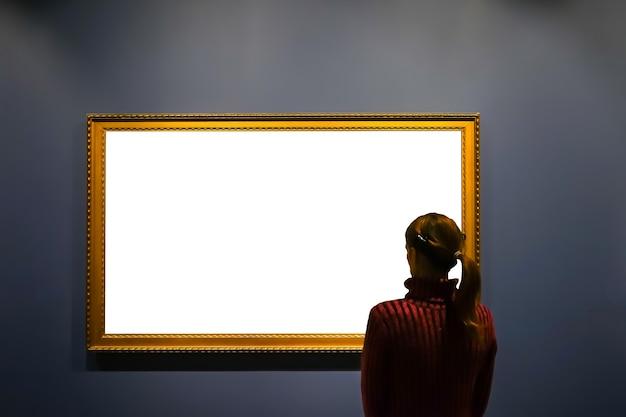 Frau im galerieraum mit blick auf leeren bilderrahmen - mock-up-kunstkonzept.