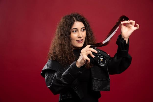 Frau im ganzen schwarzen outfit, das ein fotoband mit einer kamera hält.