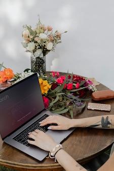Frau im garten arbeitet an ihrem laptop