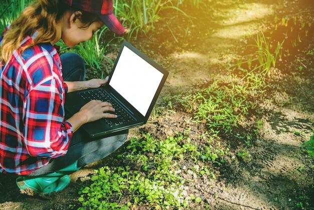 Frau im garten mit dem laptop