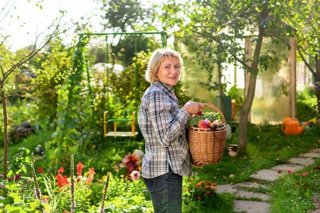 Frau im garten mit einem korb mit frischem gemüse aus dem garten