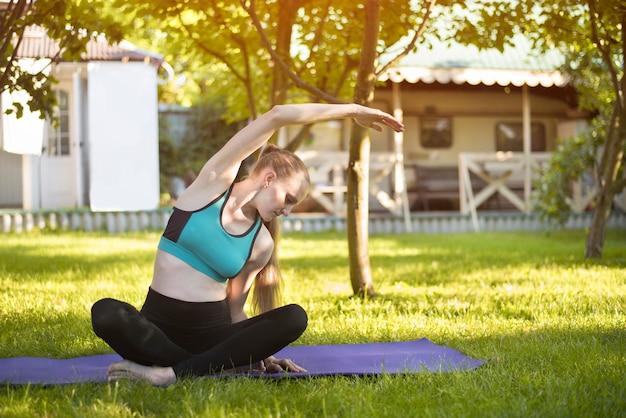 Frau im garten übt yoga. sommermorgen.