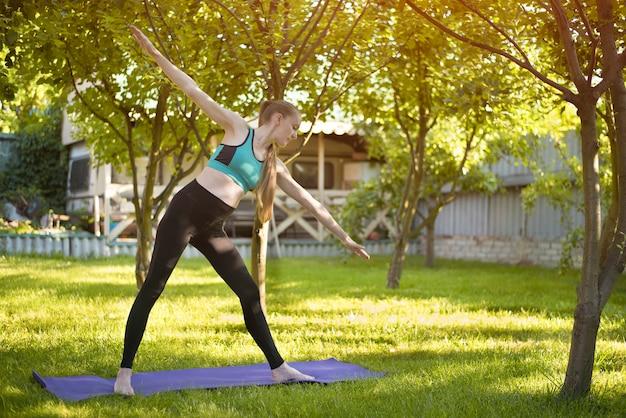 Frau im garten übt yoga. stell das dreieck auf. sommermorgen.