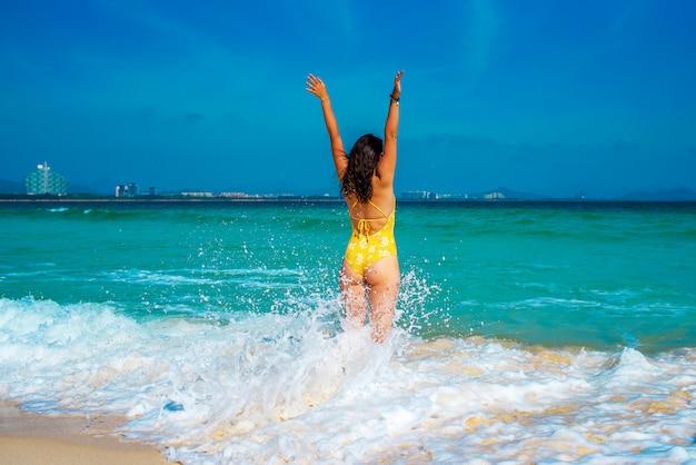 Frau im gelben badeanzug springt freudig auf die wellen im meer.