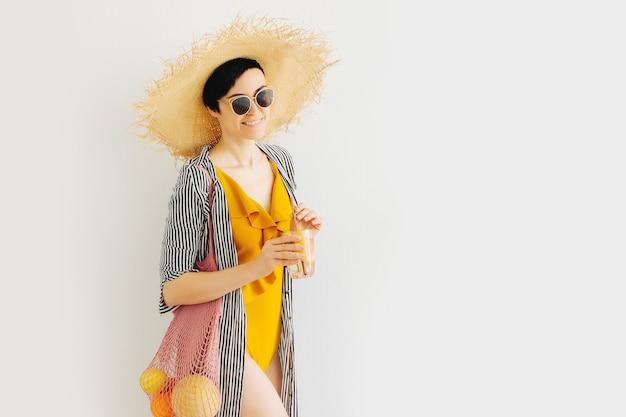 Frau im gelben badeanzug und strohhut mit netzbeutel mit früchten und cocktail auf weißem hintergrund