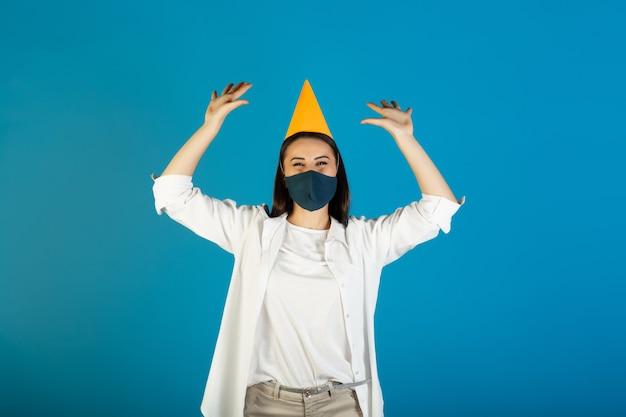 Frau im gelben geburtstagshut und in der medizinischen maske feiert ihren geburtstag während der coronavirus-zeit.