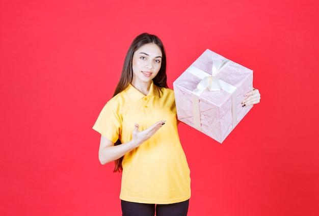 Frau im gelben hemd, das eine rosa geschenkbox hält.