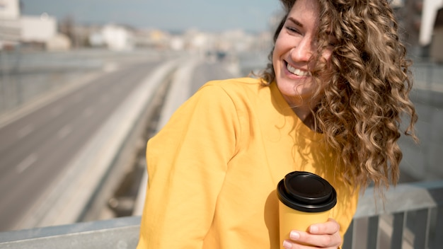 Frau im gelben hemd, das eine tasse kaffee hält