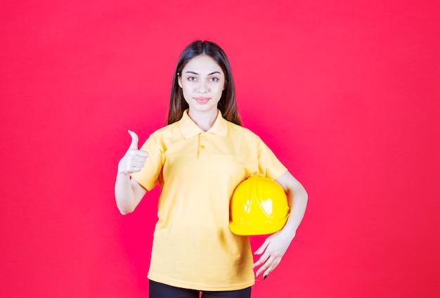 Frau im gelben hemd, das einen gelben helm hält und das produkt genießt.