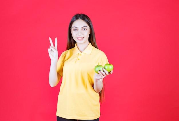 Frau im gelben hemd, das einen grünen apfel hält und zufrieden ist.