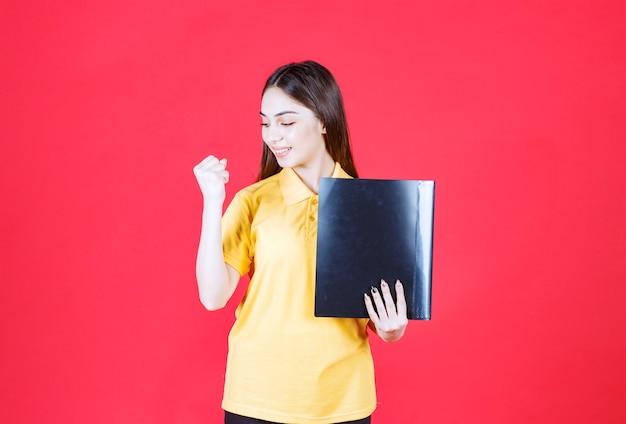 Frau im gelben hemd, das einen schwarzen ordner hält und positives handzeichen zeigt.