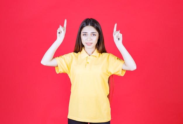 Frau im gelben hemd, die auf roter wand steht und herum zeigt.
