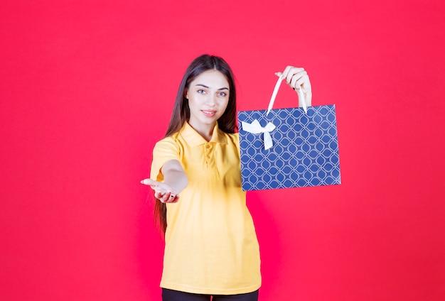 Frau im gelben hemd, die eine blaue einkaufstasche hält und den kunden zur übergabe einlädt.