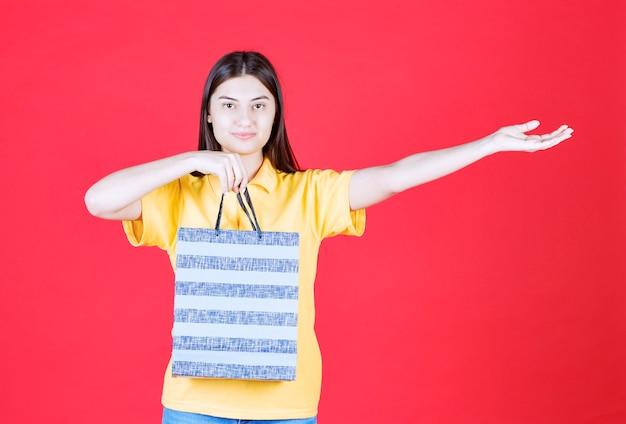 Frau im gelben hemd, die eine blaue einkaufstasche hält und jemanden anruft, sich zu nähern, um es zu nehmen.